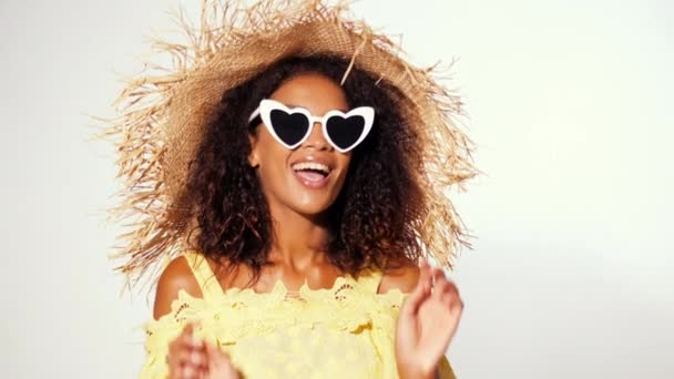 Happy african american woman with afro hair in yellow dress, sunglasses and straw hat contagiously laughs over white wall background. Girl having fun, flirting, smiling to camera.