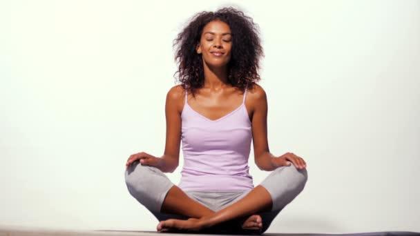 glückliche afrikanisch-amerikanische Frau in bequemer Sportkleidung meditiert auf Matte über weißem Wandhintergrund. schwarzes Mädchen konzentriert sich auf Yoga-Praxis.