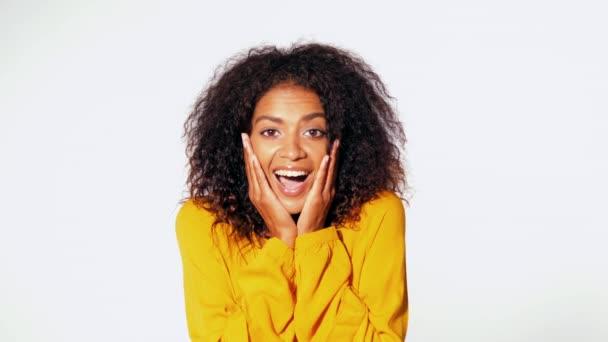 Krásná africká americká žena s afro vlasy v žluté oblečení s úsměvem, příjemně překvapen nad pozadí bílé zdi. Roztomilé Smíšené rasy portrét dívky s úžasem