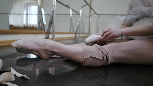 Young ballerina in beige costume kneading legs before putting on ballet shoes pointe. Woman preparing for dance training lessons in gym. Slow motion