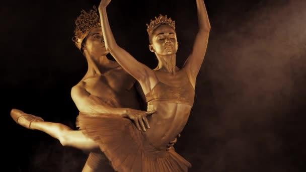 Ballerini di balletto professionale, emotivo con corone su scena fumo scuro eseguita da coppie sessuali re e la regina con golden body art. Pelle oro brillante. Slow motion