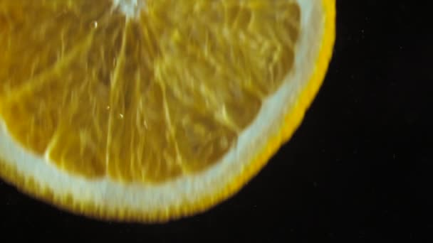 Super close up footage. Macro view. Sliced juicy fresh orange falling into water in slow motion. Bubbles on black background.