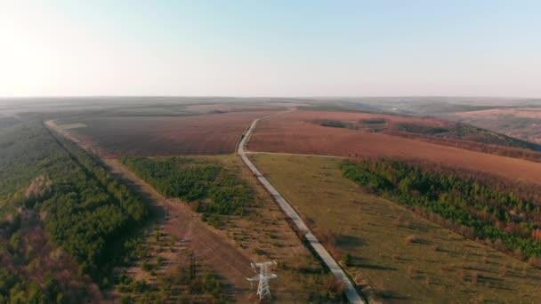 Letecký pohled stromů a pole na obzoru. Kinematografická tónovaný. DRONY střela letící nad asfaltové silnici. Krásná podzimní sezóny. Kopce a elektrické vedení