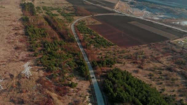 Letecký pohled na auto jízda tobogánem serpentinách. Kinematografická tónovaný. DRONY střela letící nad elektrickými vodiči a asfaltové silnici. Krásný podzim