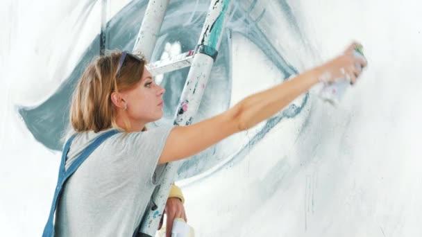 Krásná mladá dívka tvorba graffiti s Aerosolový sprej na městské ulici zdi. Filmové záběry tónovaný. Výtvarného umění. Talentovaný student v džínové overaly kreslení obrázek