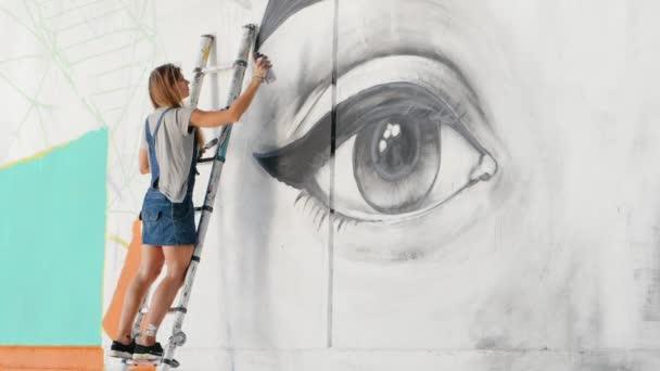 Krásná dívka, tvorba graffiti velké ženské tváře s Aerosolový sprej na městské ulici zdi. Ona stojí na žebříku. Výtvarného umění. Talentovaný student v džínové overaly kreslení obrázek