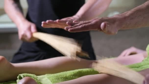 Žena relaxační masáž ve wellness salónu. Zblízka se terapeut rukou masírovat ženské nohy s bambusovými holemi roller terapie. Volný čas. Dívka se těší okamžiky. Zpomalený pohyb