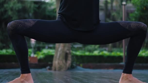 Girl doing Utthita parsvakonasana. Young woman with oriental appearance practicing yoga alone on wooden deck in tropical island. Sport, fitness, healthy lifestyle concept.