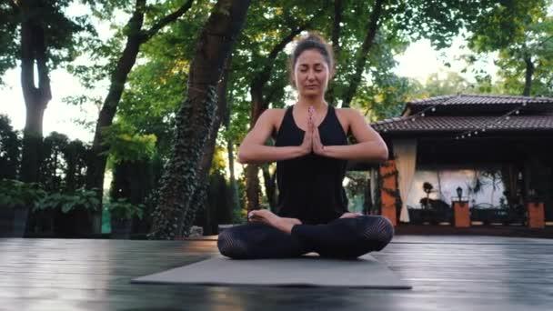 hübsche Frau mit orientalischem Gesicht, die Yoga praktiziert, namaste Dankbarkeit Mudra allein in tropischen Insel. Mädchen in Lotuspose. Religion, Reinheit, Resignation, Spiritualitätskonzept. Padmasana.