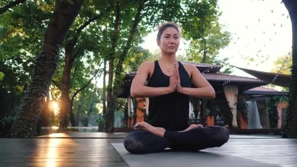 Konzentriertes Mädchen, das in Lotus-Pose sitzt, die Hände in Namaste und meditiert oder betet. junge Frau mit orientalischem Aussehen praktiziert Yoga allein auf Holzdeck in tropischen Insel