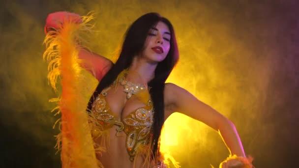 verführerisch sexy traditionelle orientalische Bauchtänzerin Mädchen, das auf gelbem Neon-Rauch-Hintergrund tanzt. Frau in exotischem Kostüm mit Federn bewegt ihren halbnackten Körper sexuell.