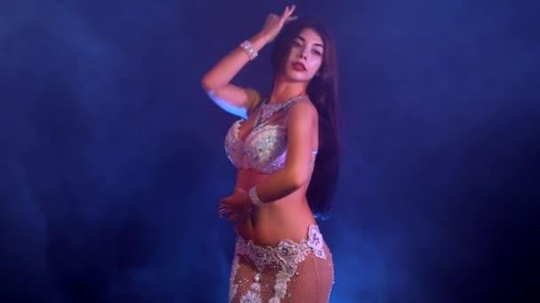 Frau in exotischen Kostümen bewegt sich sexuell halbnackten Körper. Sexy traditionelle orientalische Bauchtänzerin Mädchen tanzen auf blauen Neon Wand. Muslime, Versuchung Konzept. Spektakuläre show