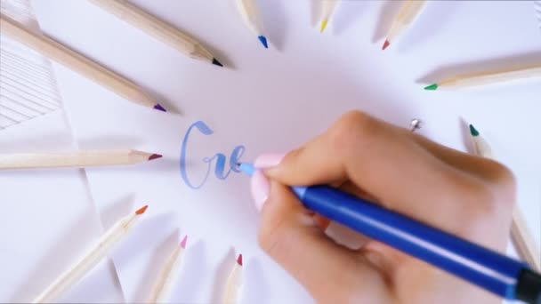 Create. Female hand writes beautiful blue letters on canvas in colorful pens frame. Calligraphy script. Art of writing letters. Woman sitting on old white wooden table. Background.