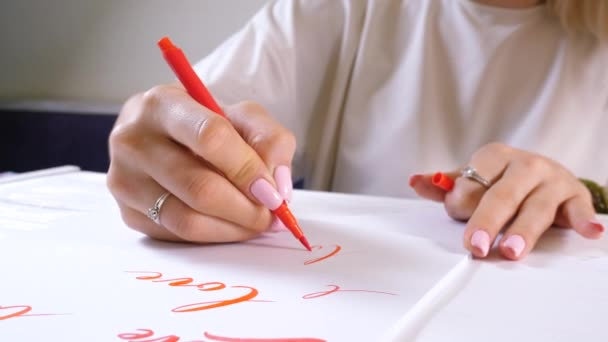 Calligrapher student practices in writing word LOVE with red marker on canvas. Creative artist freelancer working on project at home studio. Lettering, handwriting concept. 4k.