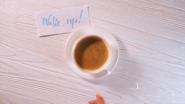 Wake up text. Font of lettering word on white paper with blue ink by calligrapher. Female hand takes cup of coffee from table. Morning, handwriting, lettering, concept.