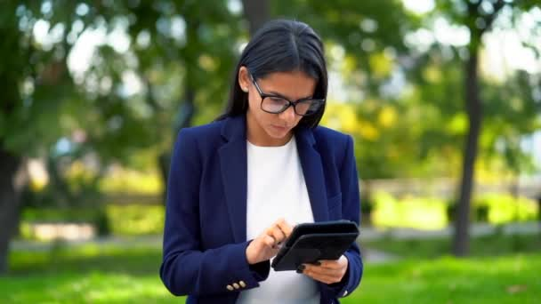 Successful business woman with tablet computer on green park background. Beautiful girl in formal wear and glasses surfing internet or working on electronic device