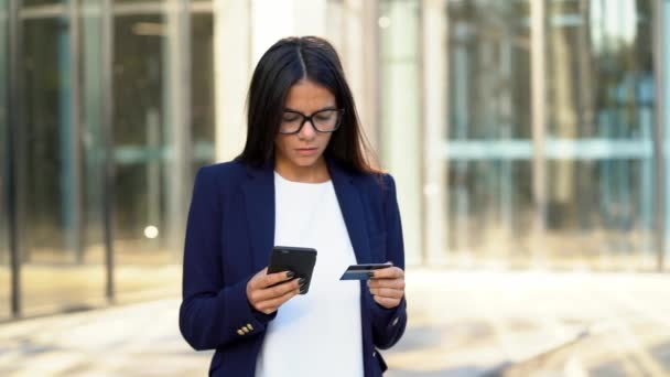 Fiatal szép üzletasszony vagy banki segítségével neki smartphone irodaház háttér a tanuló. Online vásárlás, adósság-visszafizetési, pénz fogalma.