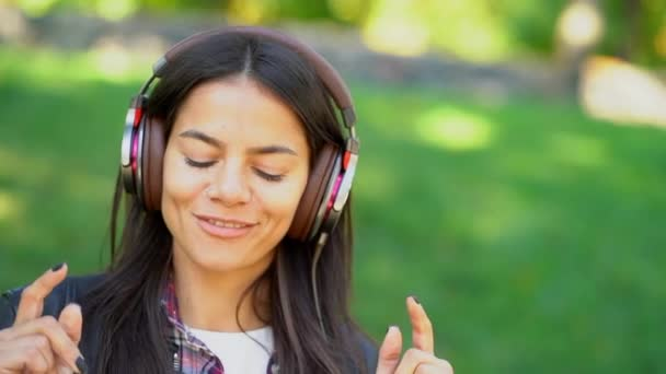 Happy Smíšené rasy mladá žena poslechu hudby ve sluchátkách. Hispánský bokovky dívka tančí do rytmu a zpívají melodii v parku. Kopírovat prostor.