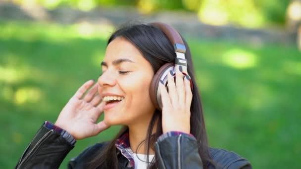 Happy Smíšené rasy mladá žena poslechu hudby ve sluchátkách. Hispánský bokovky dívka tančí do rytmu a zpívají melodii v parku