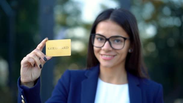 Úspěšné ženské pohled na kameru a zobrazeno neomezený gold kreditní kartou na kancelářskou budovu pozadí. Hospodáře žena nosí brýle a oblek
