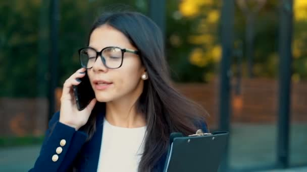 Businesswoman have conversation using mobile phone. Business girl in glasses and formal suit talks intently with colleague. Office employee, wage worker, weekdays concept