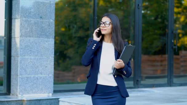 Businesswoman have conversation using mobile phone. Business girl in glasses and formal suit gladly talks with colleague. Office employee, wage worker, weekdays concept.