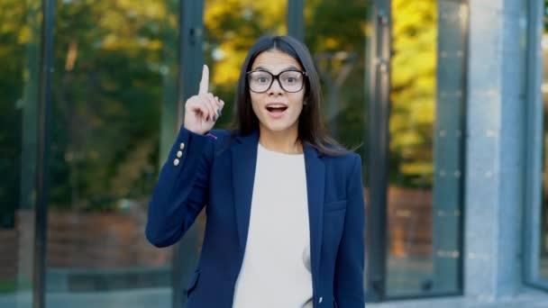 Usmíval se šťastný student dívka ukazuje Heuréka gesto. Portrét mladé myšlení zamyšleně podnikatelka s myšlenkou chvíli ukazující prst na kancelářské budovy pozadí