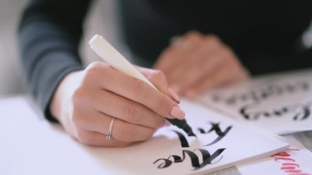 Closeup of calligrapher hands writes phrase on white paper. Inscribing ornamental decorated letters. Calligraphy, graphic design, lettering, handwriting, creation concept. 4k.
