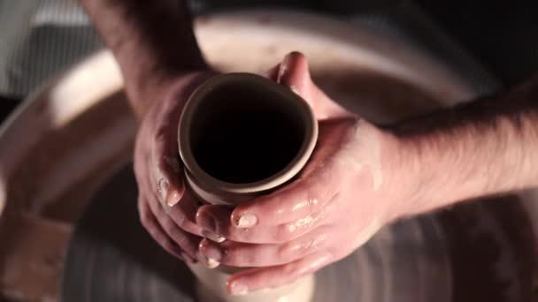 Draufsicht der Mann, der Topf auf der Töpferscheibe. Töpfer formt das Ton Produkt - Vase oder einen Becher - mit professionellen Werkzeugen, Ansicht von oben. Inhaber eines kleinen Unternehmens in Werkstatt