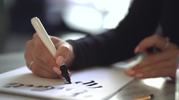 Hands of young woman sitting in cafe or studio and writing beautiful font phrase on white paper. Handwriting, lettering, calligraphy concept. Girl working on creative project