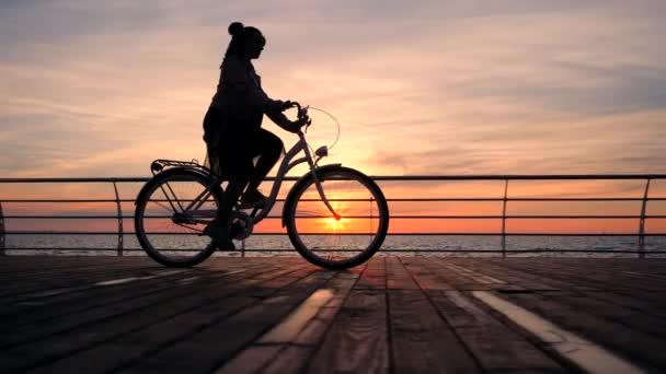Nádherný východ nebo západ slunce nad oceánem. Silueta dívka stylové cyklistické na vintage kolo na dřevěných nábřeží. Žena na kole poblíž moře. Zpomalený pohyb. 4k
