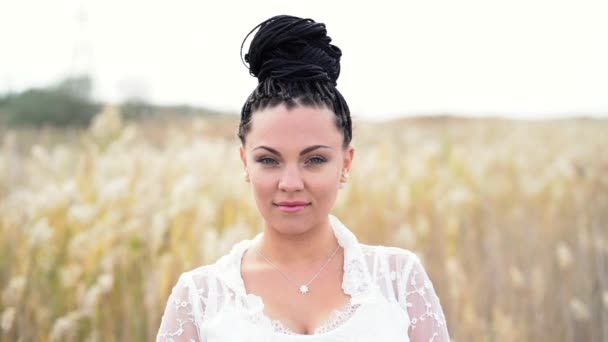Portrait of young beautiful woman with african braids hairstyle standing in reeds field. Autumn season. Gypsy girl in boho-bohemian lace white dress looking at camera and smiling