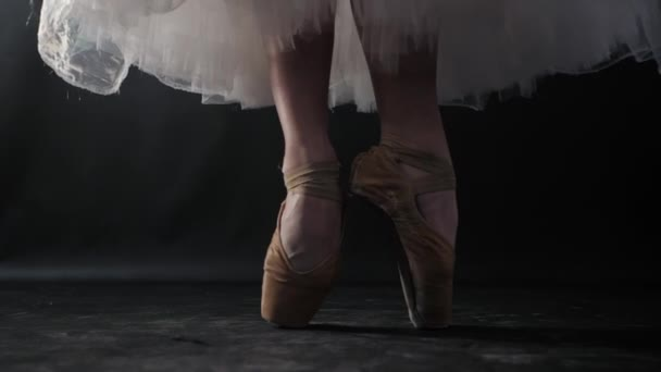 Close up of ballet dancer as she practices exercises on dark stage or studio. Womans feet in pointe shoes. Ballerina shows classic ballet pas. Slow motion. Flare, gimbal shot