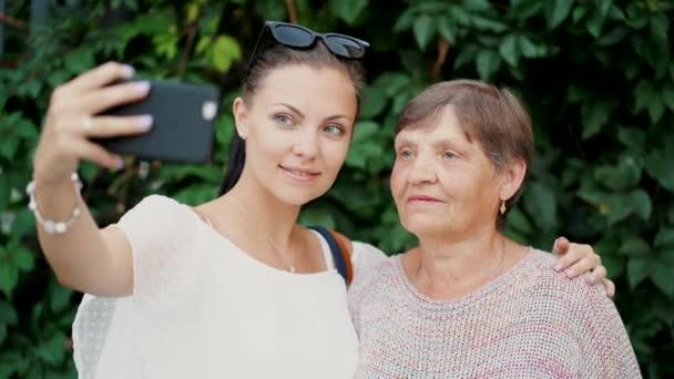 Krásná stará babička a její vnučka dělá selfie venkovní na pozadí listoví, při pohledu na fotoaparát a usmívá se smartphone fotoaparát. Technologie, koncepce paměti.