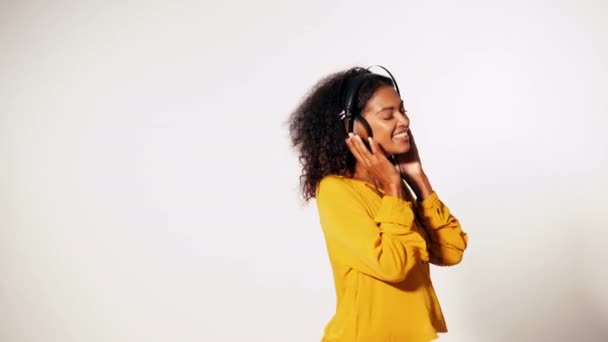 Attractive african-american young woman listening to music with headphones and dancing on white wall background. Girl in yellow fall top. Studio footage. Music concept. Slow motion