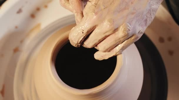 Creating earthenware traditional pottery concept. Experienced male potter hands.