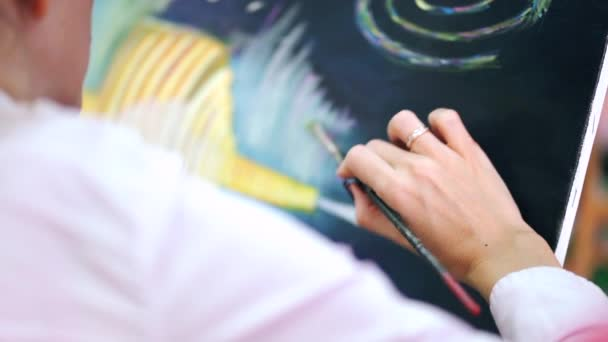 Womans artist hands drawing picture with oil paints on canvas.