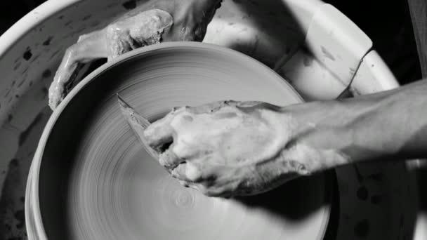 Zkušeným hrnčířem obrazce jíl produkt mísa s keramikou Nástroje. Zavřít z mužských rukou pracovali hrnčíři kola, zarovná povrch desky. Černá a bílá tonned