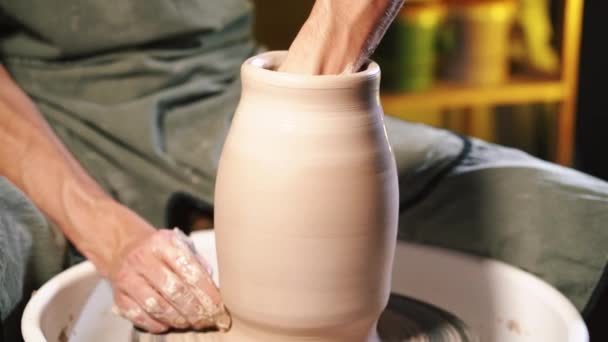 Muž pracuje rukama s jílem. Proces vytváření výrobků z hlíny na hrnčíři kola. Boční pohled řemeslník hrnec nebo džbán. Majitel malé firmy v dílně