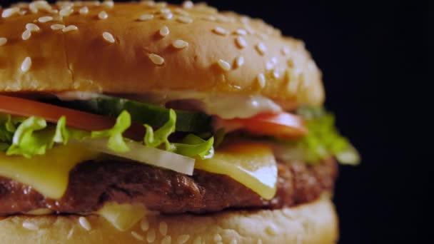 Chutné rychlé občerstvení koncepce. Čerstvé domácí grilovaný burger s maso patty, rajčata, okurka, hlávkový salát, cibule a sezamová semínka. Nezdravý životní styl. Jídlo pozadí.