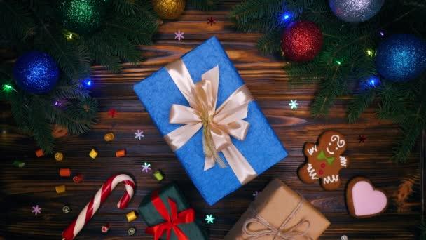Slavnostní složení dárek vánoční ozdoby na dřevěné plochy pozadí. Pohled na ploché ležel, top. Nový rok dovolená rámec větví, dar, soubory cookie, lízátko hole, sladkosti