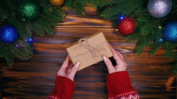 Mette le mani ragazze regalo avvolto in carta del mestiere e spago arco nel centro del telaio realizzato con rami di abete. Decorazioni di Natale - lampeggianti garland, bagattelle. Vista dallalto