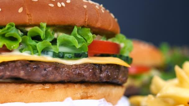 Velké chutné burger s řízek masa, zeleninu, sýr, ledový salát a omáčka. Hamburger se otočí na jiné jídlo pozadí, detailní zobrazení. Koncept nezdravých dobrot