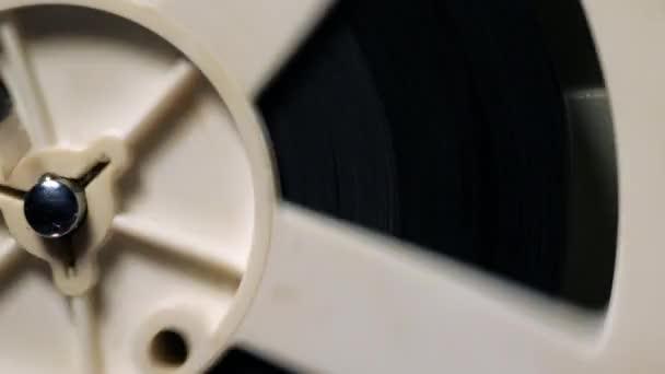 Egy tekercs részlete. Projektor találat film régi 8 mm-es film a sötét szobában éjszaka. Lassú mozgás. Vintage retro tárgyak, előhívott koncepció