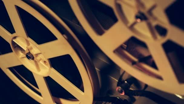 Navijáky s otáčejícím se filmu zavřete zobrazení. Vintage objekty, kinematografické koncepci. Retro filmový projektor v temné místnosti. Staromódní starožitný super 8mm film projektor