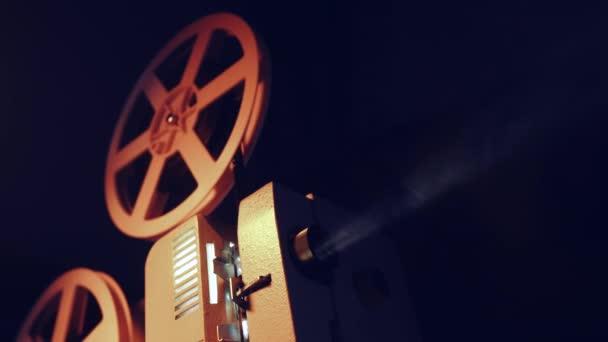 Vintage-Objekte, Cinematograph-Konzept. Retro-Filmprojektor, der im dunklen Raum spielt. altmodische antike Super-8mm-Filmprojektor projiziert Lichtstrahl. 4k.