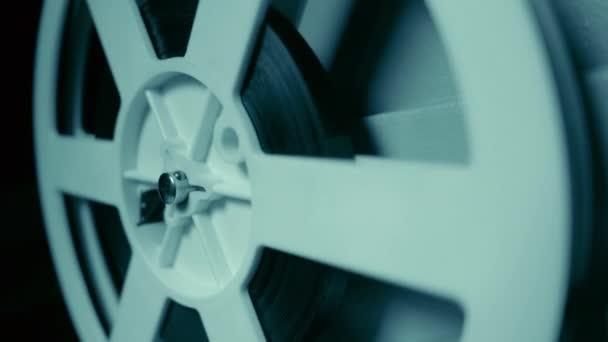 Közeli kép a spinning reel. Projektor találat film régi 8 mm-es film a sötét szobában éjszaka. Lassú mozgás. Vintage retro tárgyak, előhívott koncepció