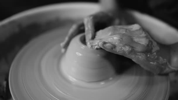 Mann arbeitet seine Hände mit Lehm. Prozess der Erstellung Produkt aus Ton auf der Töpferscheibe. Seitenansicht der handwerklichen Herstellung Topf oder Krug. Kleinunternehmer in Werkstatt. Schwarz / weiß