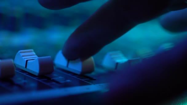 Hand eines Tontechnikers, der mit Fader am Mischpult bei Musikkonzerten arbeitet. Nahsicht. buntes Neonlicht