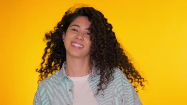 Female having fun. She smiling, hair flutter beautifully. Amazing positive footage. Girl moves to the rhythm of music. Woamn with curly hair dancing on yellow background.